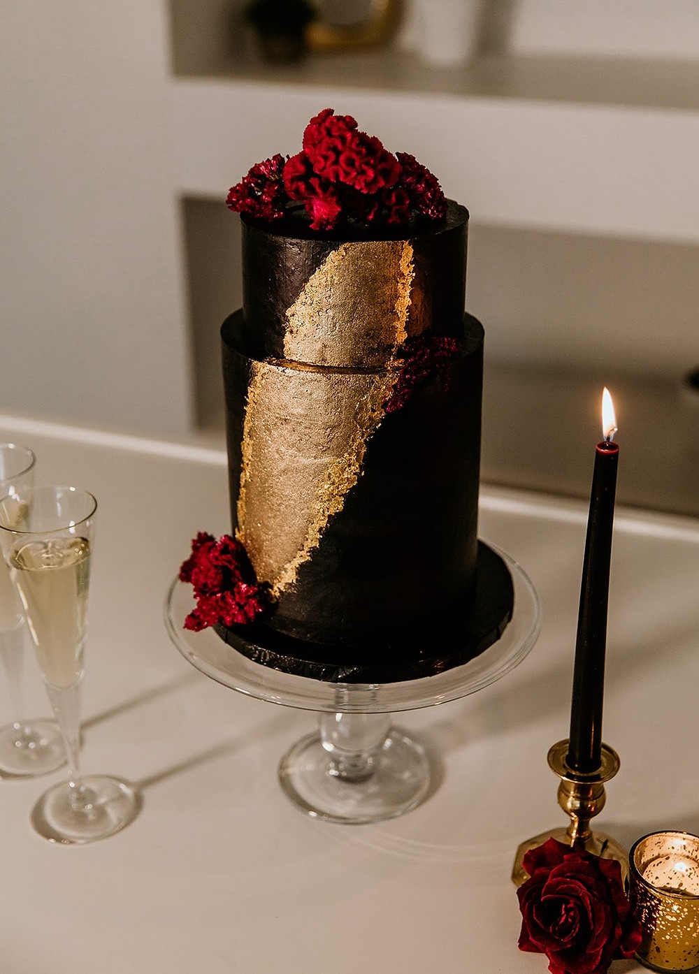 Black and gold wedding cake with burgundy flowers