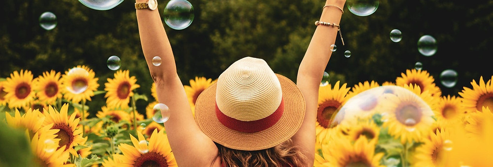 Girl raising her hands in joy among sunflowers and bubbles