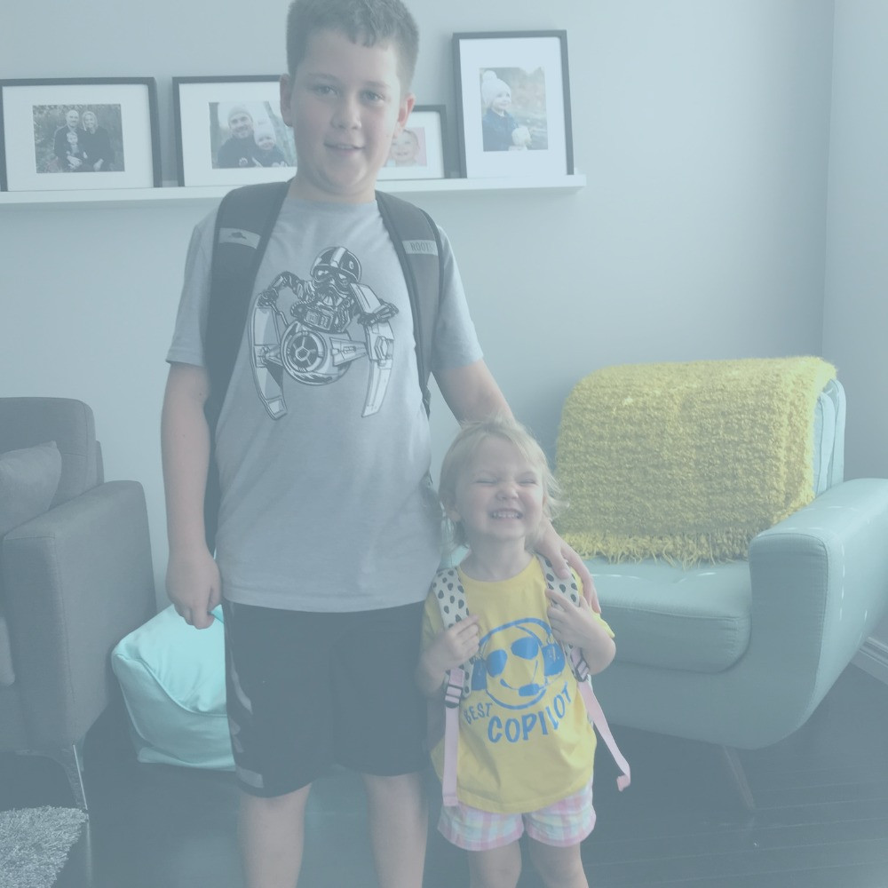 Older boy and sister smiling at camera with their backpacks before the first day of school