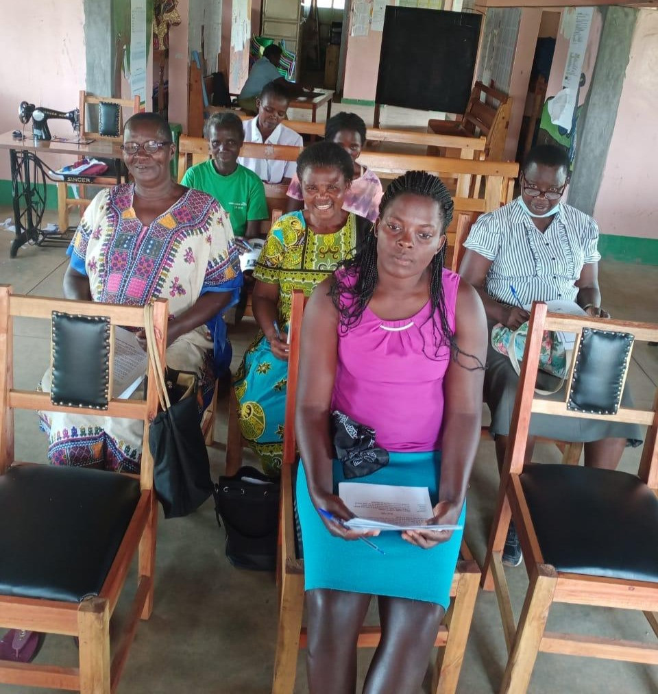 Women from a Kenya village smiling and sitting together for an online conference