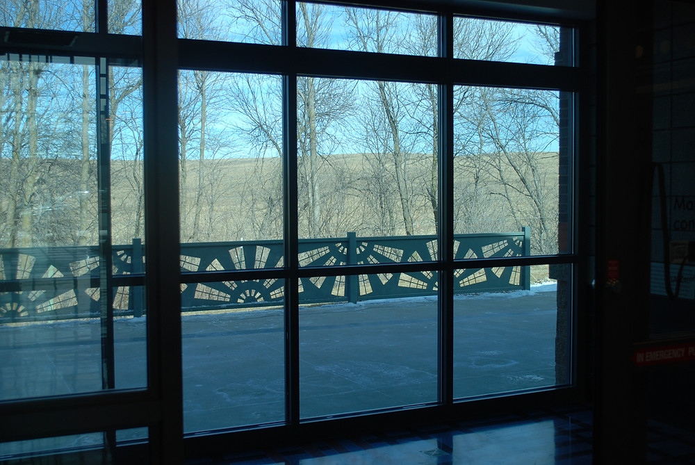 A glass doorway and window overlooking a rest area balcony with a  metal railing with a windmill blade pattern, trees in the background.. Patterns of rectangles over rounded windmill blades with fractal branching trees in winter in the background.