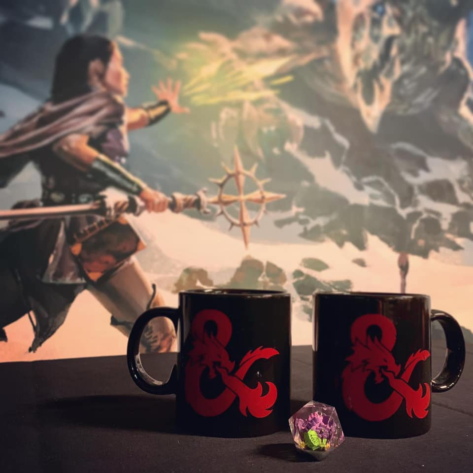 DOTS dragon d20 on a table with D&D ampersand logo mugs in front of giant poster showing D&D essentials kit box art of adventurer casting a spell at a dragon.
