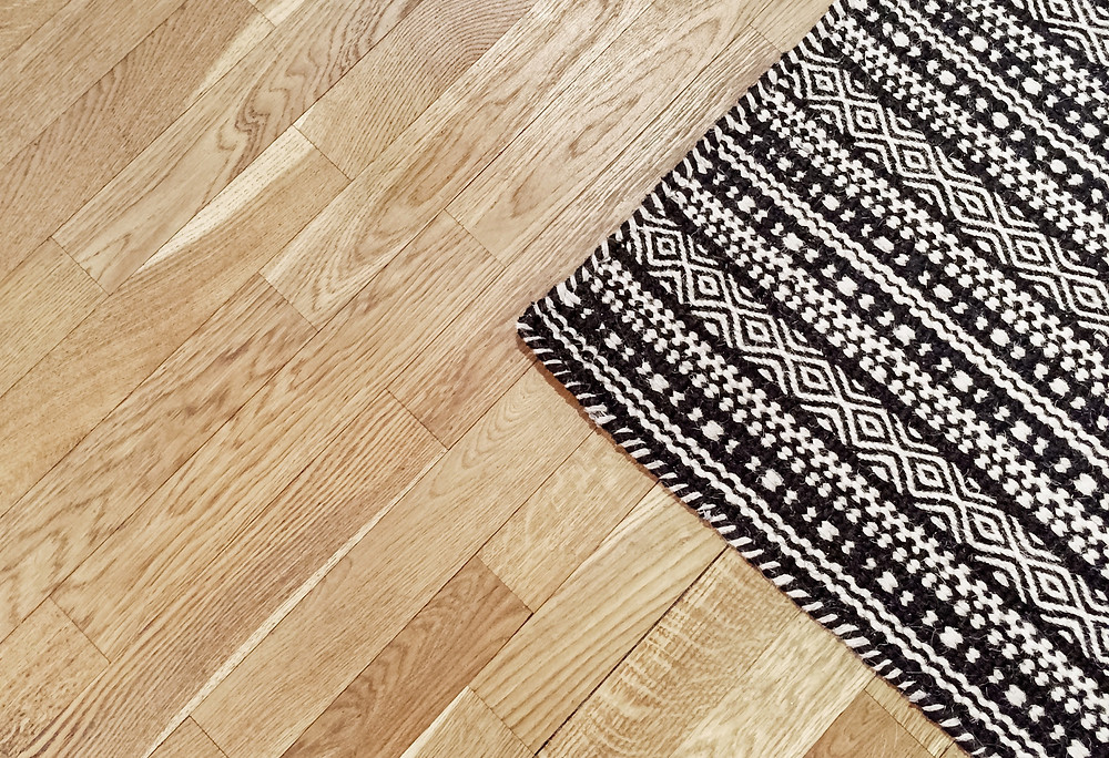 Black and white welcome mat on top of hardwood floor