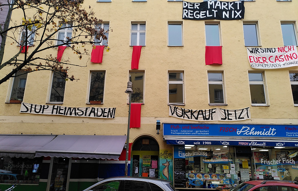 Banners on a house in Kreuzberg read 'Stop Heimstaden', 'Der Markt regelt Nix' (the market regulates nothing), 'Wir sind nicht euer Casino' (we are not your casino), and 'Vorkauf jetzt' (pre-buy now, a reference to the mechanism under which the state can block the sell-off of housing by stepping in to purchase property itself)