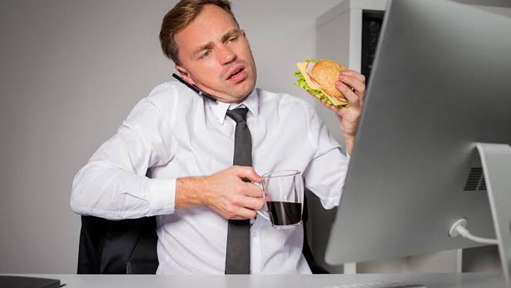 Hombre comiendo frente a la computadora.