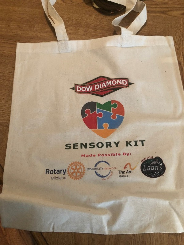 sensory tote bag for dow diamond featuring heart with different colored puzzle pieces and the logos of midland noon rotary, the ARC of Midland, the Great Lakes Loons and Disability Network