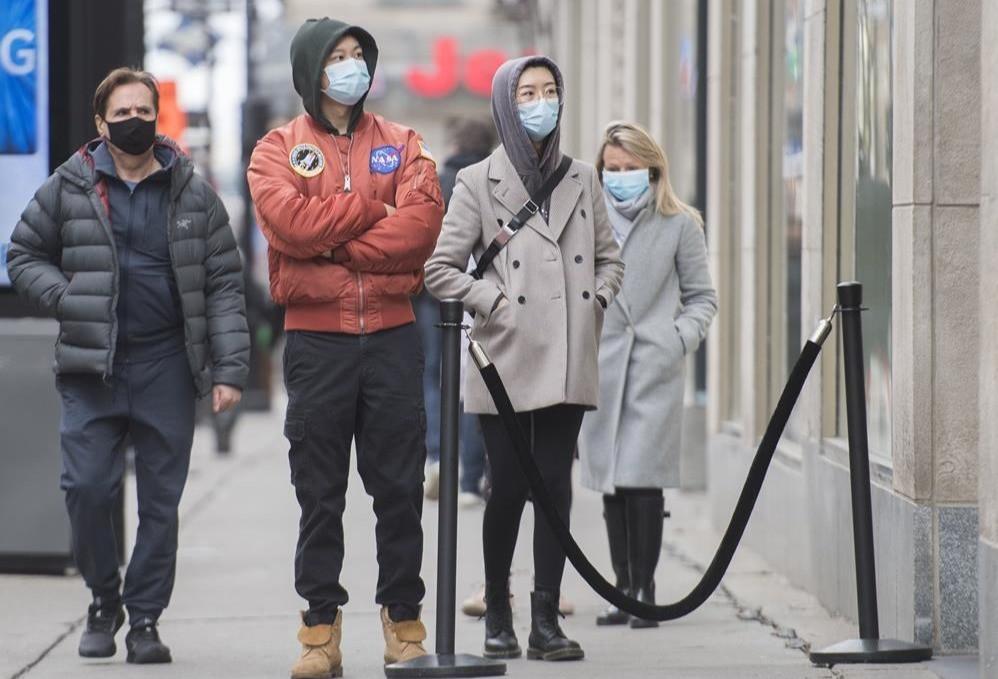 Las personas usan máscaras faciales mientras esperan ingresar a una tienda en Montreal, el sábado 14 de noviembre de 2020.