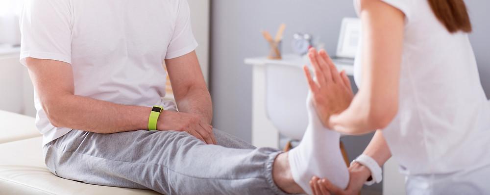 Homem em sua casa sentado na cama recebendo fisioterapia de uma Fisioterapeuta do CIP que atende a domicílio