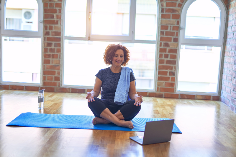 Woman in yoga studio looking at laptop
