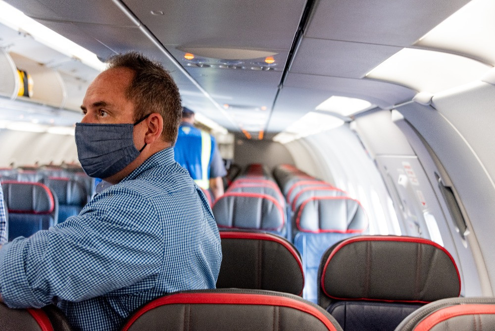 A man wears a mask as he boards an American Airlines plane.