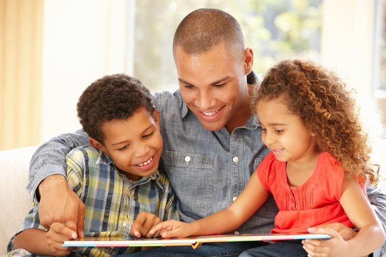 Таткото седи со своите син и ќерка на претшколска возраст и заедно разгледуваат сликовница