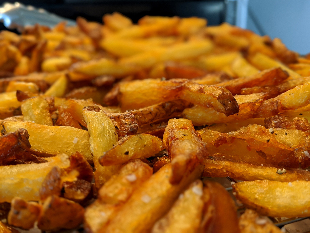 Hot frites out of the fryer seasoned with kosher salt and freshly ground pepper