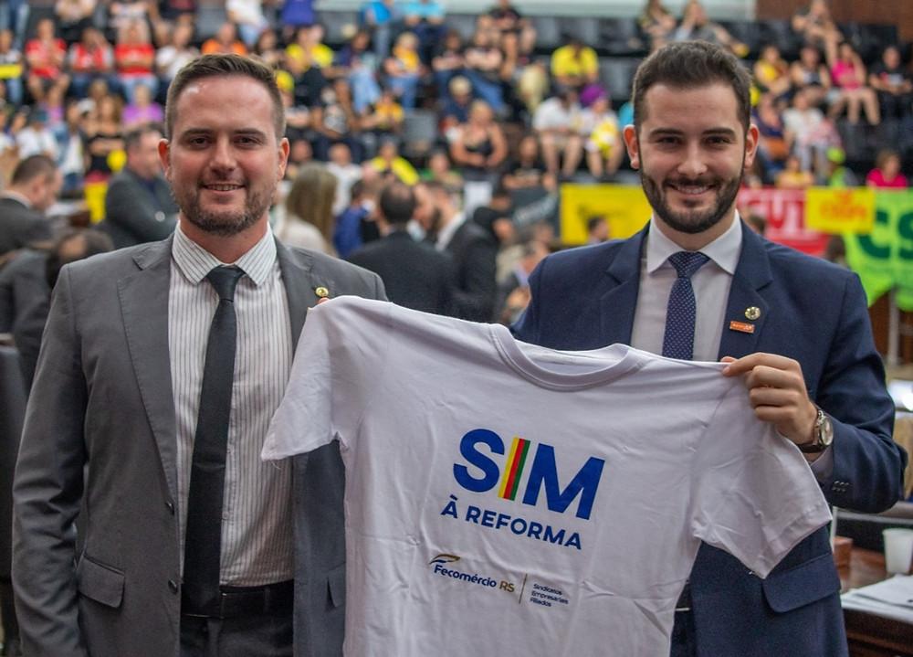 fábio ostermann e giuseppe riesgo sorrindo segurando camiseta com dizeres de sim à reforma
