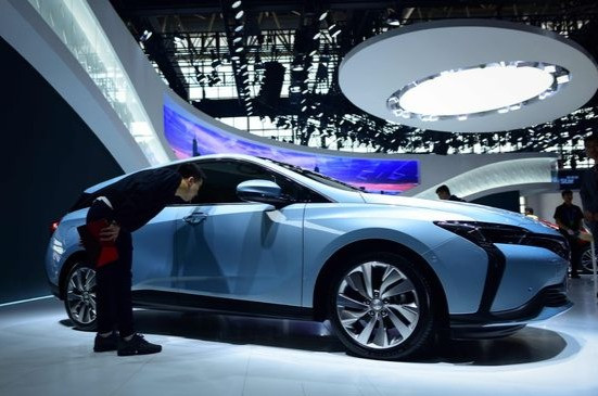 Man looking into the passenger's side window of a Hybrid Buick Velite 6 at Beijing auto show.