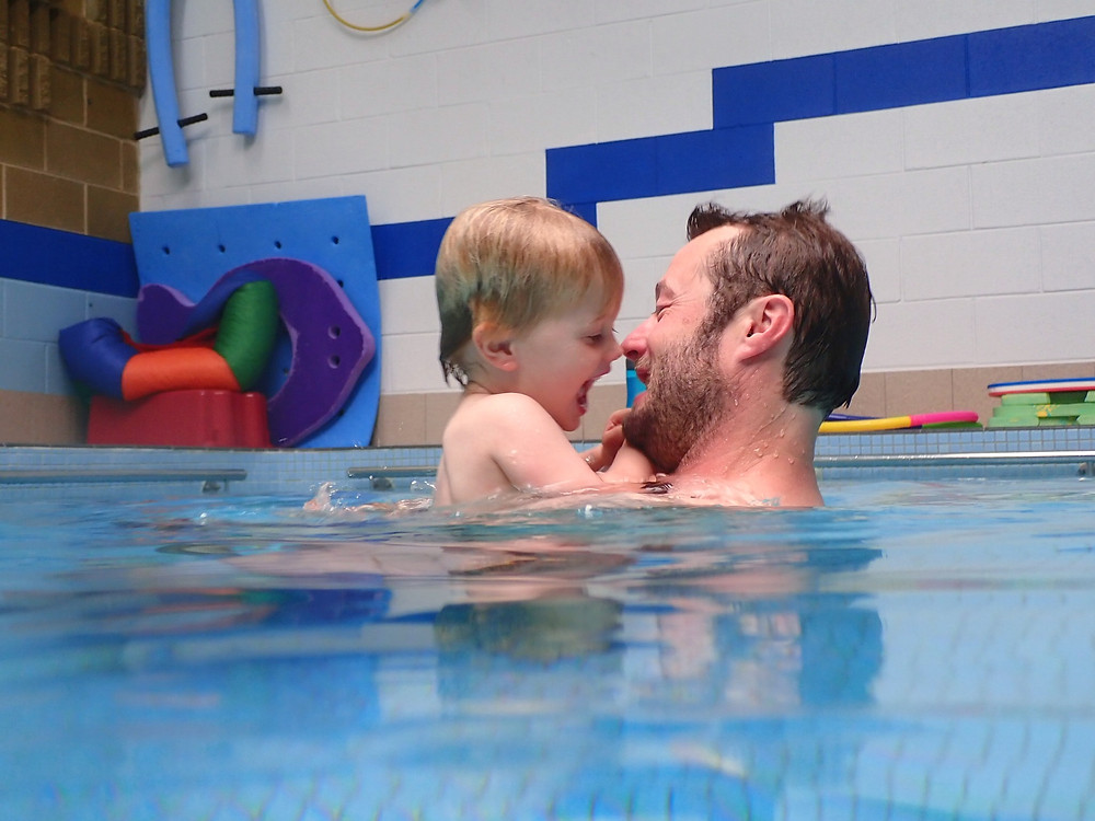 baby with his father playing together in the pool face to face