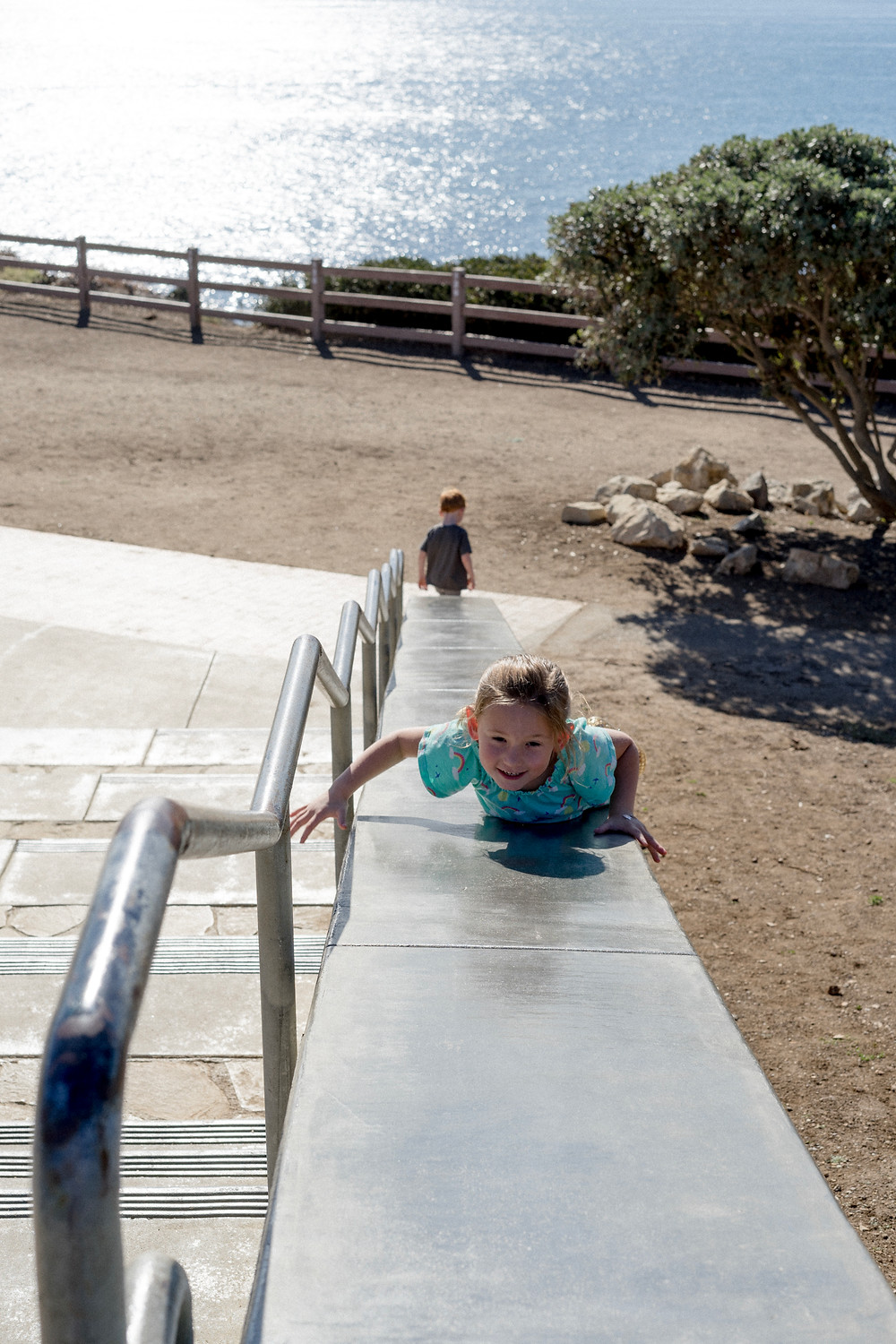 Young girl sliding down a slide, looking back at the camera
