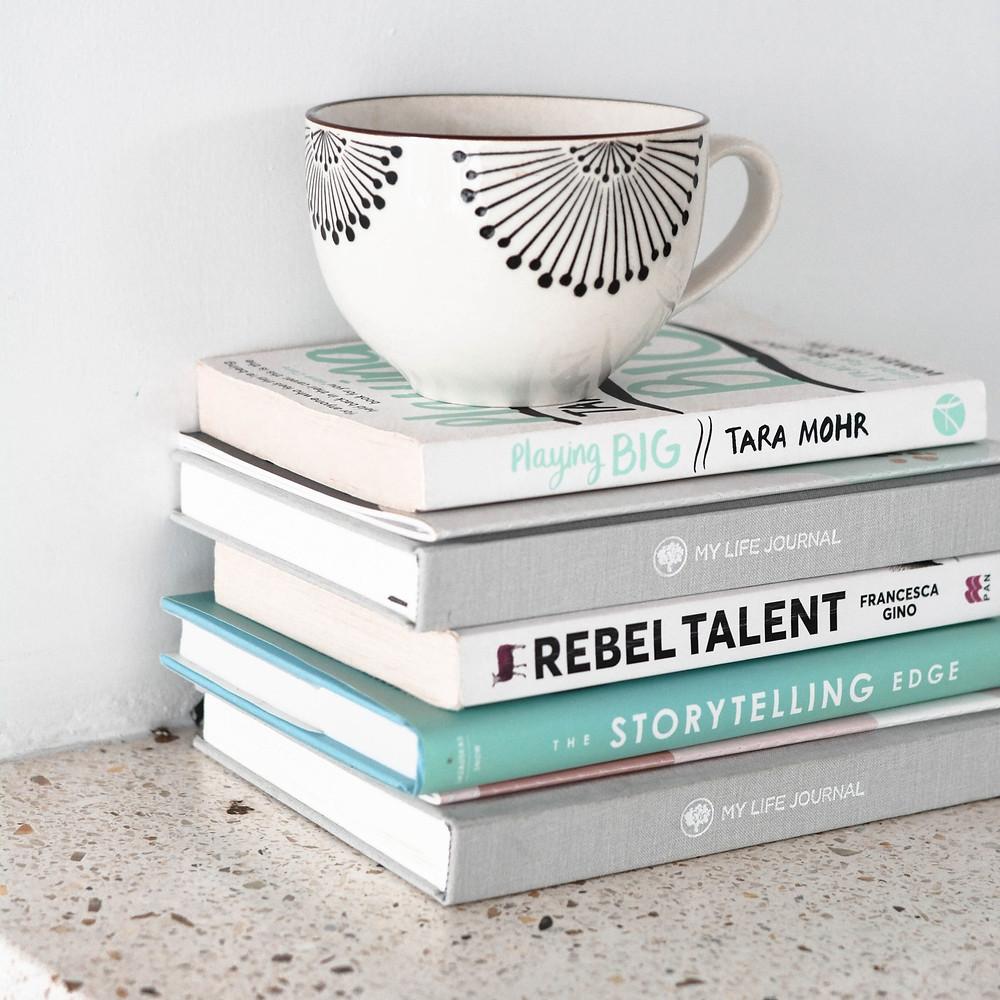 Sete livros organizados em uma pilha, nos tons de cinza, verde, branco e preto. Eles estão sobre uma mesa de tampo salpicado de cinza. Sobre os livros, uma caneca branca com detalhes em forma de leque, em preto.