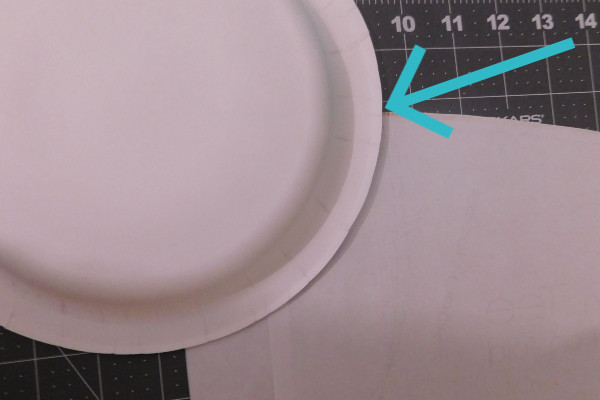 Image shows the back of the pattern piece with a paper plate laying on top. The edge of the paper plate is lined up with the upper (shoulder) edge of the pattern piece. There is a blue arrow pointing to where the paper plate and neck opening meet.