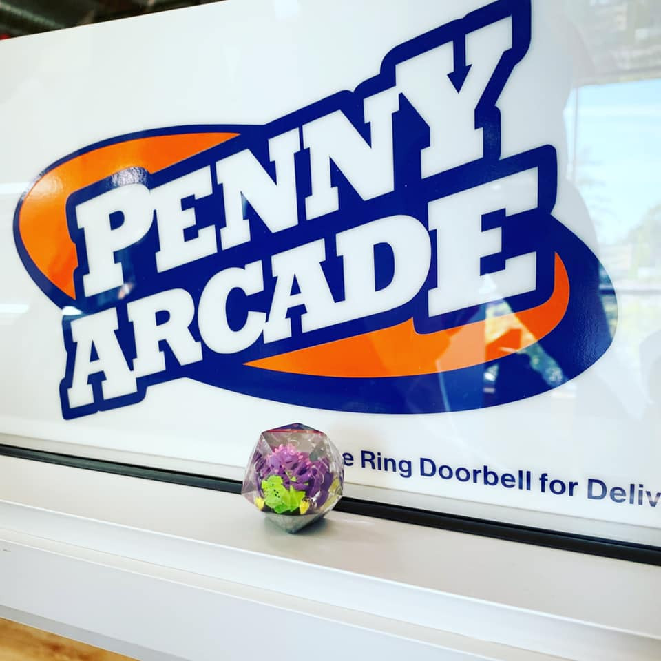 DOTS dragon figure inside clear d20 sitting in front of sign with Penny Arcade logo.