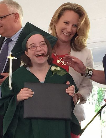 Image of Ilyse Ross, wearing her green graduation cap and gown, posing with Executive Director Michelle Theroux.
