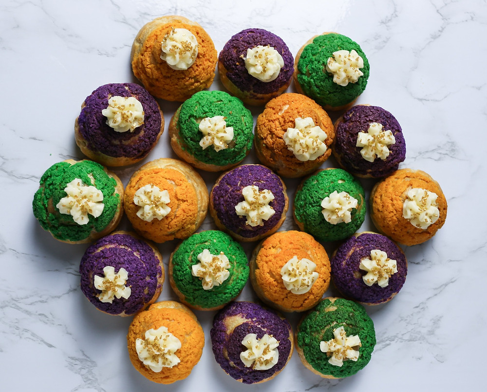 A cluster of yellow, purple and green cream puffs topped with butter cream flowers and gold sprinkles.