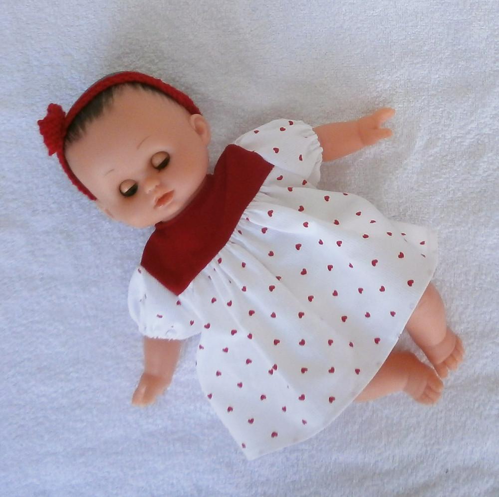 Un poupon bien sage dans sa robe à petits coeurs rouges
