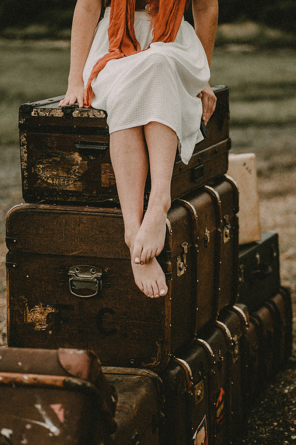 Woman sitting on top of vintage suitcases