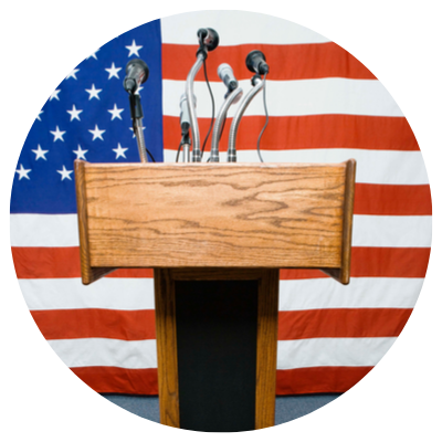 A podium with microphones in front of the American flag.