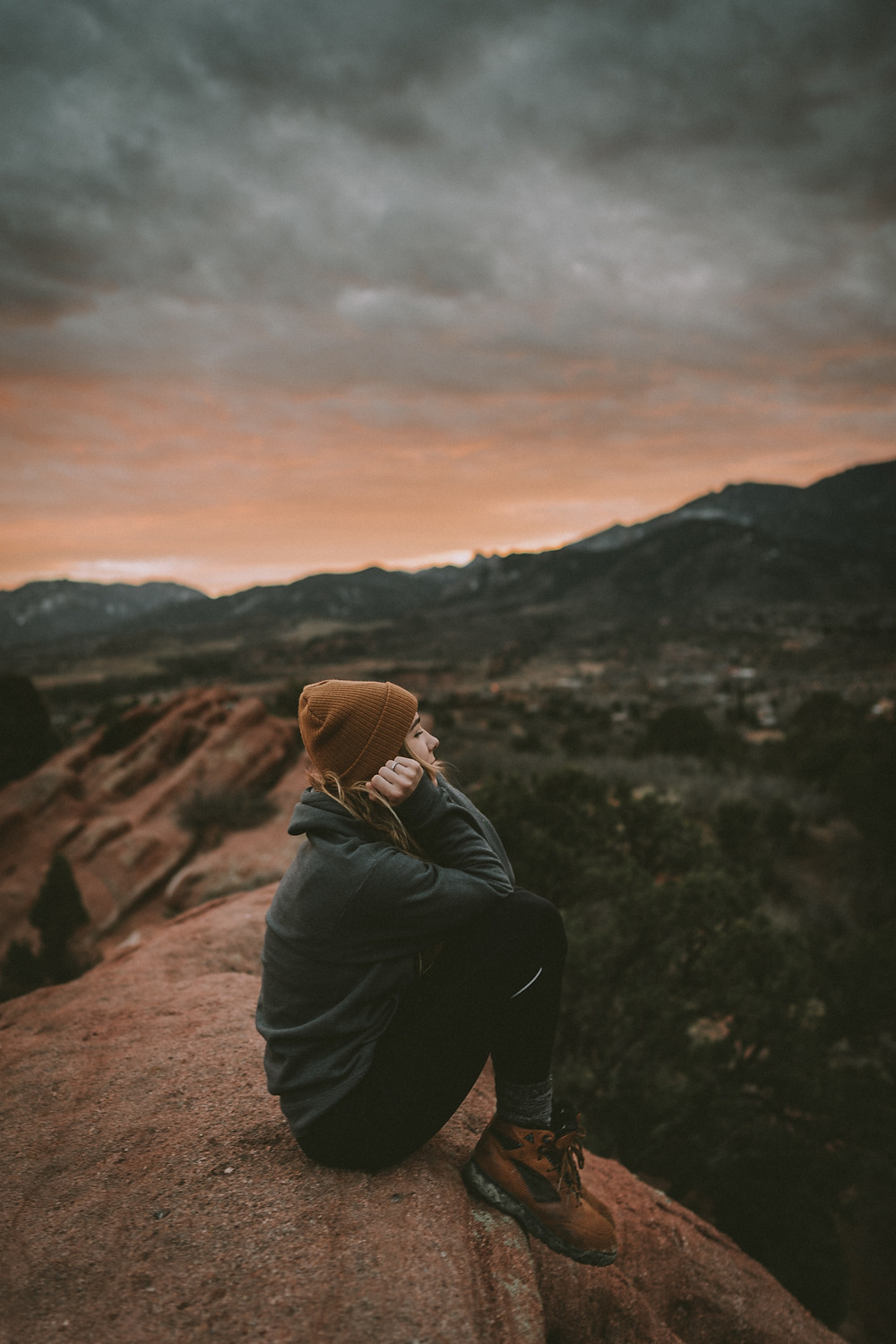 Woman sitting on a large rock in the mountains wondering if she should go to counseling during coronavirus in Englewood CO. Catalyss Counseling can meet your therapy needs in Denver CO 80209 and 80219