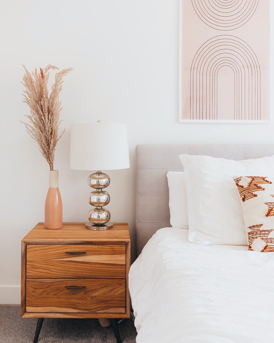 Some blush artwork hung above a bed with white linens.