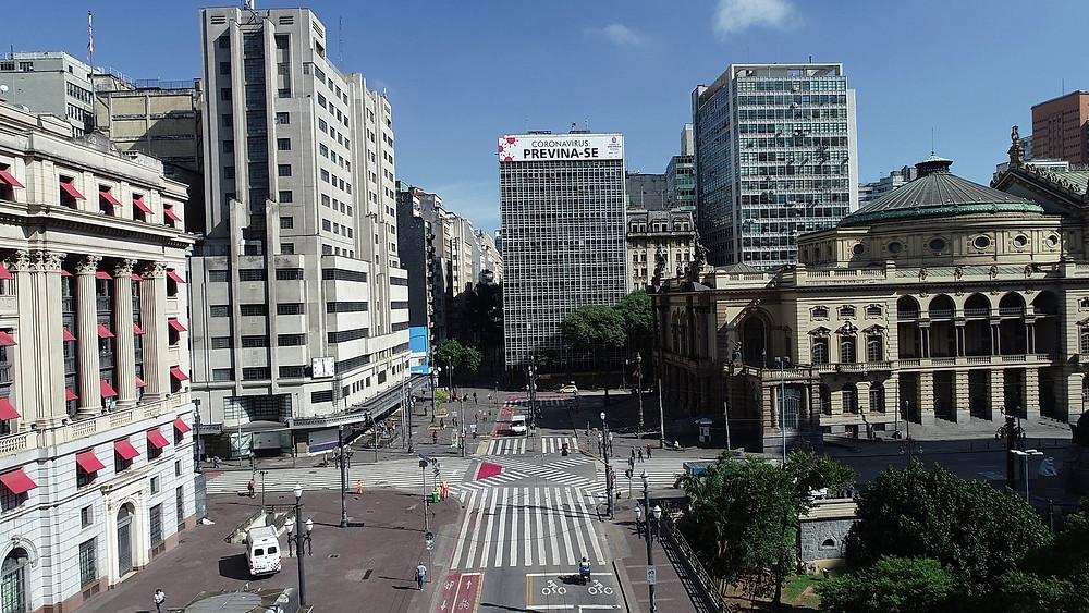 Foto do alto do mostrando poucas pessoas circulando, prédios fechados e apenas um carro. À direita, uma praça vazia e ao fundo, no alto de um prédio, uma faixa escrita em letras garrafais: Coronavírus Previna-se.