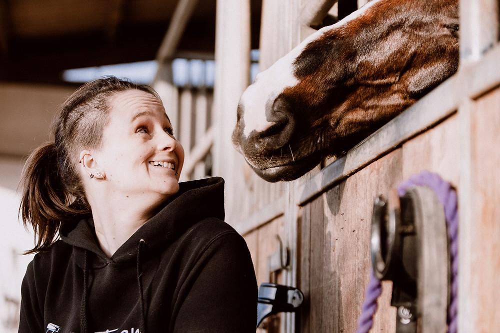Katharina blickt lächeln ein Pferd an, welches neugierig die Nase aus seiner Box streckt.