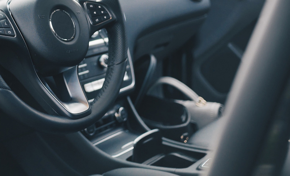Car interior featuring the steering wheel and cup holder