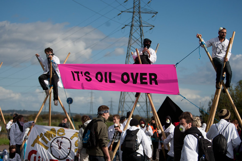 """Three people sitting on tripods above a crowd holding a pink banner saying """"IT'S OIL OVER"""""""
