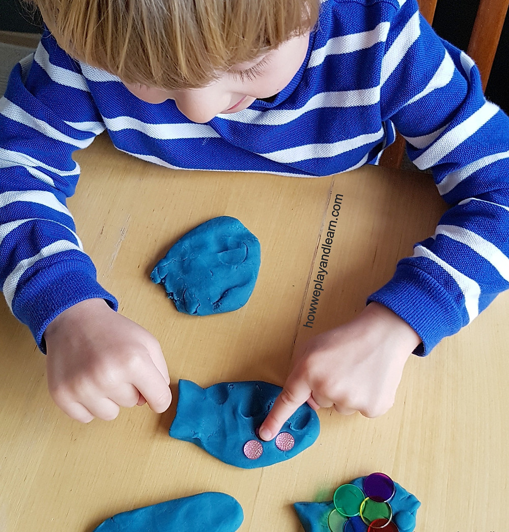 Child playing and learning with blue playdough