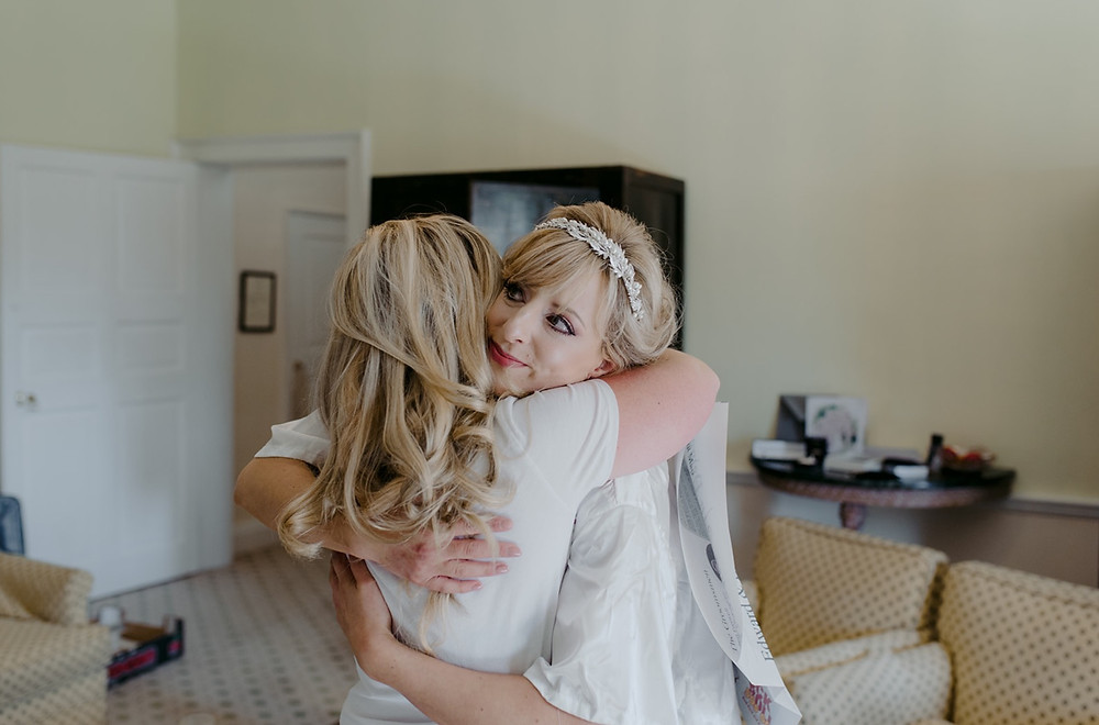 bride hugging bridesmaid wedding morning
