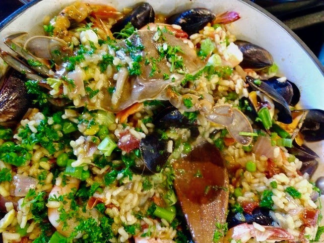 Homemade paella with crab, mussels, clams, shrimp, and fresh parsley