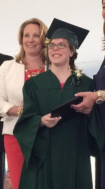 Image of Courtney Beech, wearing her green graduation cap and gown, posing with Executive Director Michelle Theroux.