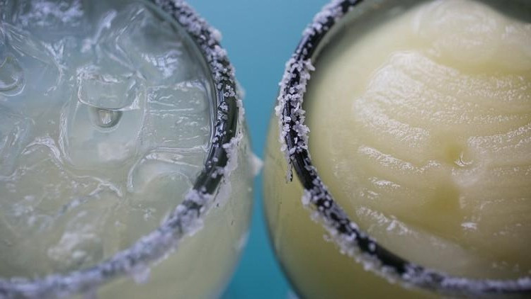 Two goblets of margaritas, with one unblended on the rocks to the left, and another on the right in a smoothie form. Both have salt along the rims.