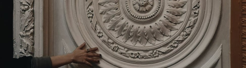 Woman's hand touching a white carving