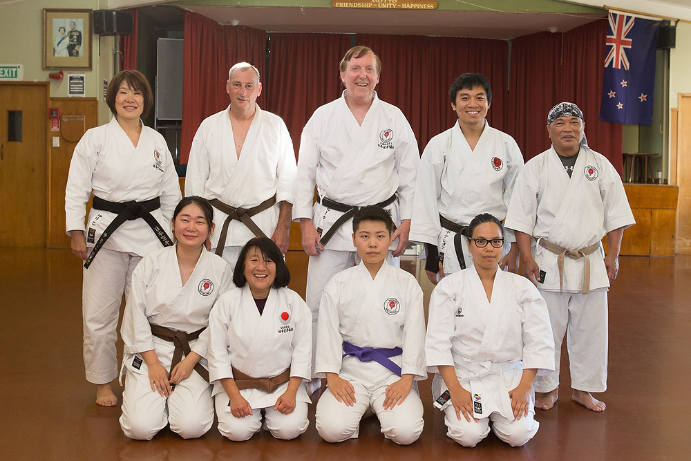 karate students, first row seated on the floor, second row standing