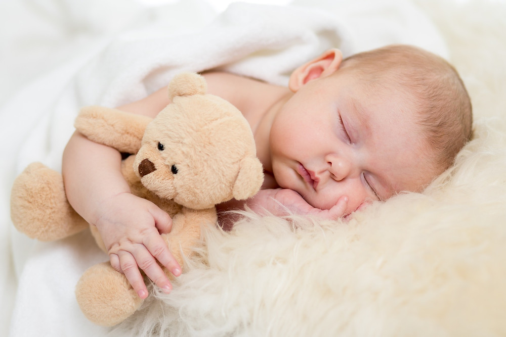 A close up of an infant sleeping with an arm around a small teddy bear.