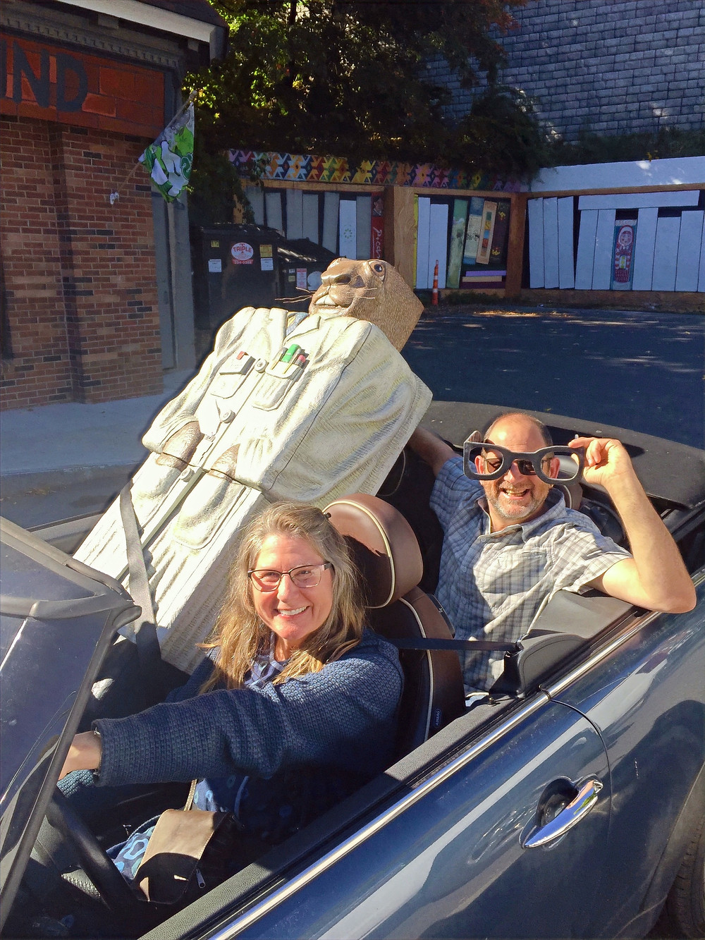 Steven in backseat of car with friend Gayle while helping her move a large piece of art