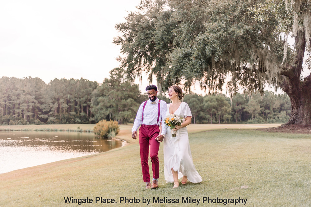 Bride and Groom walk hand-in-hand laughing by the pond at Wingate Place