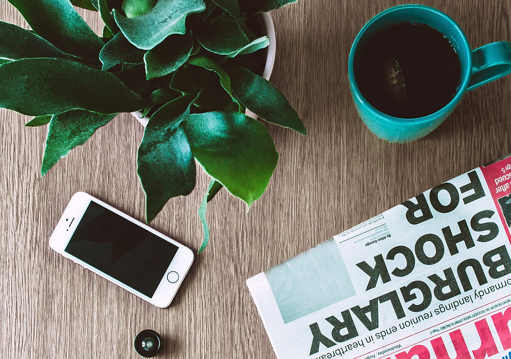A newspaper on a desk alongside a smartphone, a cup of coffee and a houseplant.