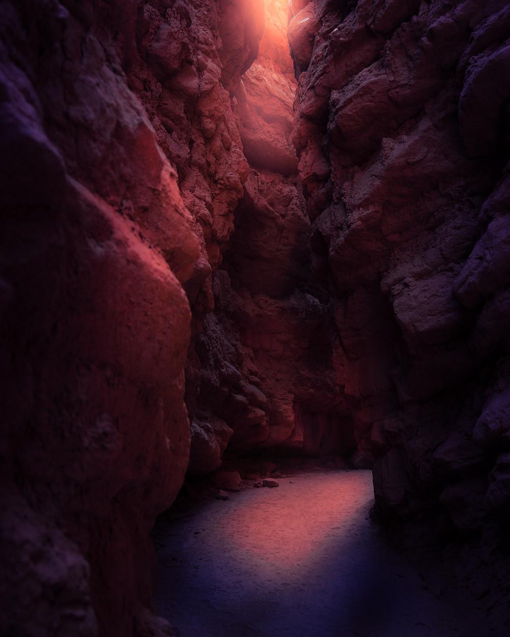light entering a dark slot canyon hiking trail
