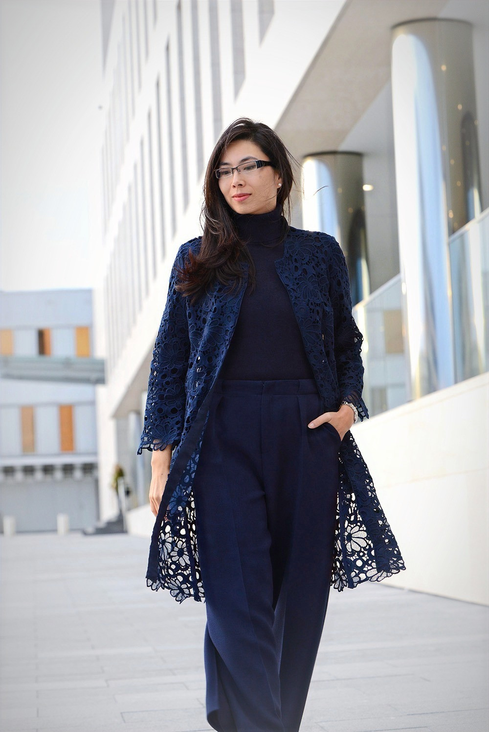 Business Casual woman outfit with a navy floral lace coat and a navy pants from Roland Mouret.