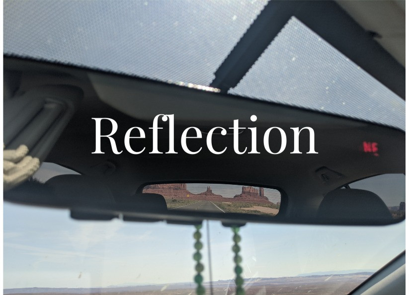 view of monument valley in the rearview mirror of a car