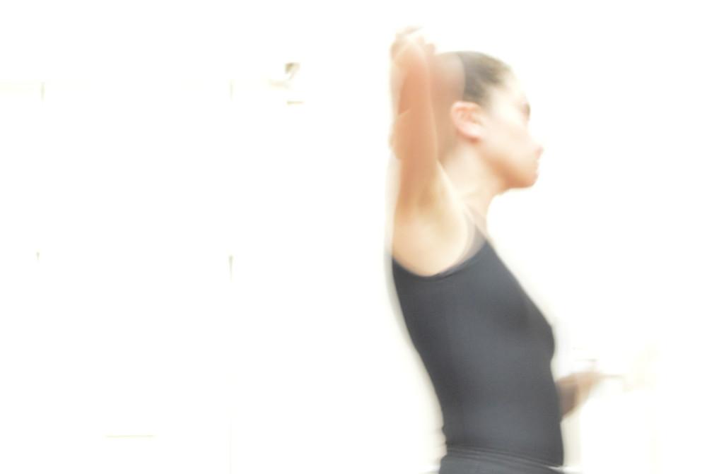 imagem de uma moça de perfil em movimento. imagem desfocada no fundo branco