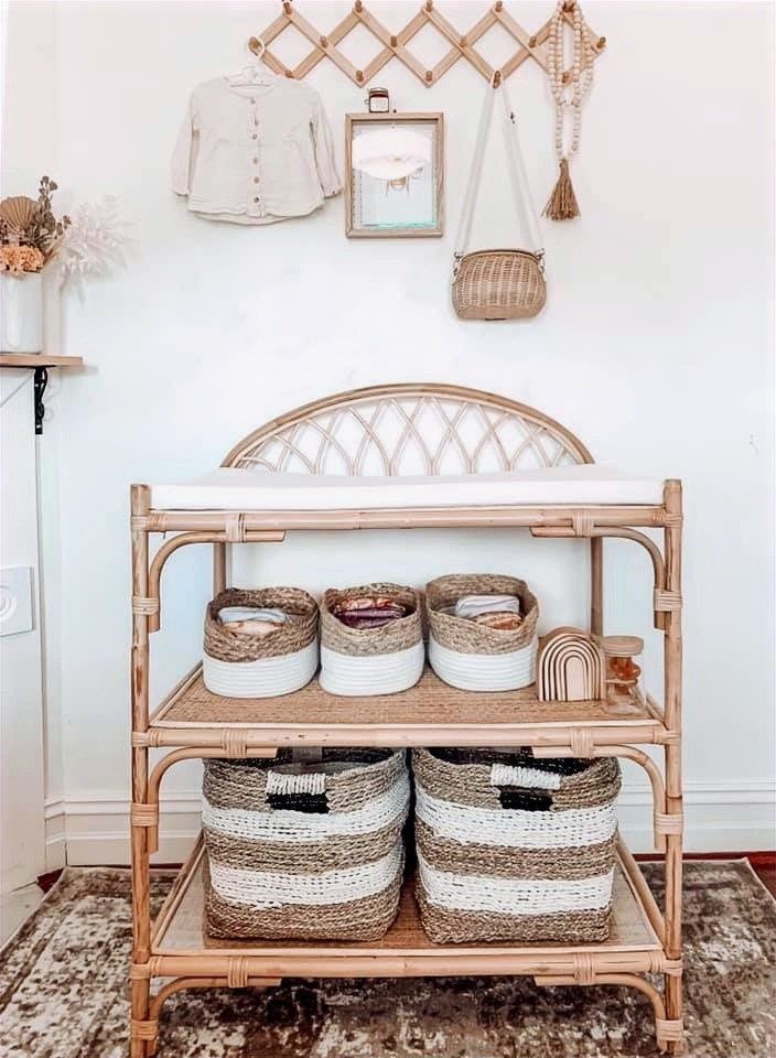 Beautiful nappy change table setup in muted earthy tones showing modern cloth nappy storage and dry pails